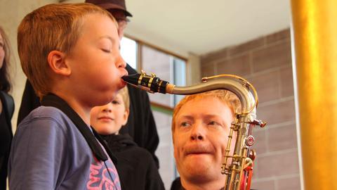 Musiker der hr-Bigband unterweist Kind