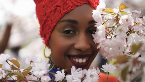 Lächelnde Frau schaut durch blühendem Busch