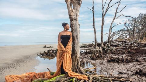 Frau lehnt an einem Baum an Strand