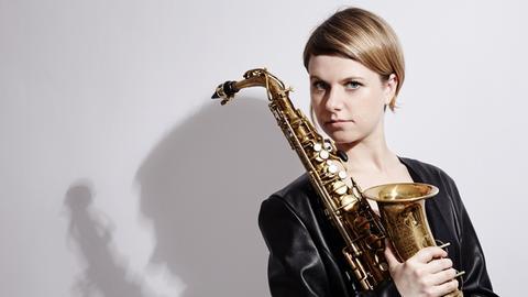 Frau mit Saxophon schaut in Kamera