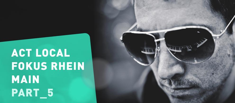 Mann mit Sonnenbrille, in der sich Klaviertastatur spiegelt und Schrift